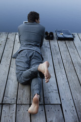 Young businessman lying on pier at lake using laptop