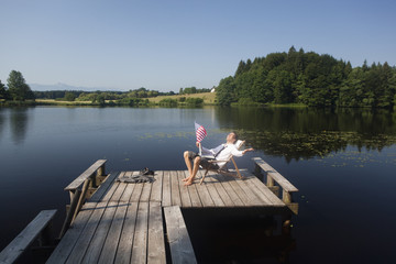 Young businessman sitting on pier at lake with American flag