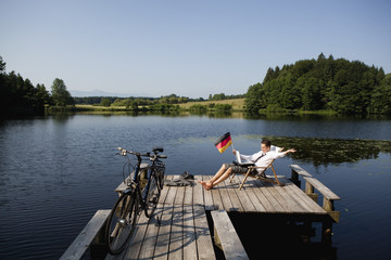 Young businessman sitting on pier at lake with German flag