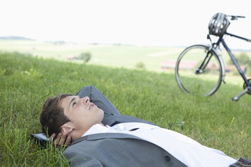 Young businessman lying in grass relaxing near bicycle