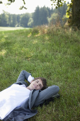 Young businessman lying in the grass relaxing