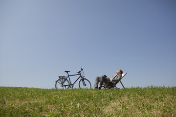 Young businessman sitting in chair in grass with bicycle