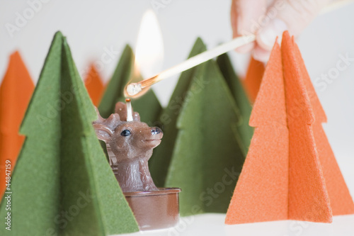 Lighting Reindeer candle with a match