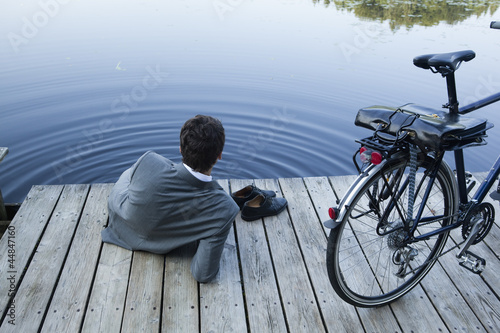Young businessman relaxing on pier at lake with bicycle