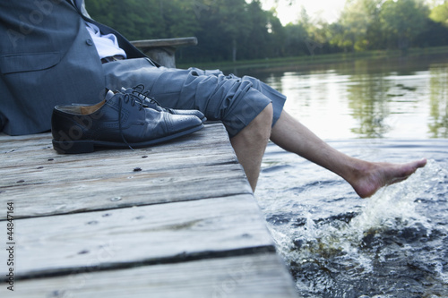 Close-up of young businessman sitting on pier at lake with feet in the water