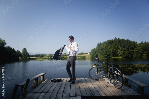 Young businessman standing on pier at lake with bicycle
