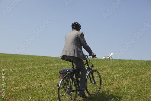 Young businessman riding bicycle in grass