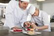 Chef teaching trainee how to garnish gourmet dessert in commercial kitchen