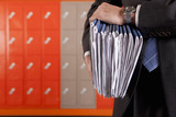 Close up of teacher holding paperwork near school lockers
