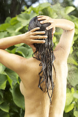 Young nude woman taking shower outdoors