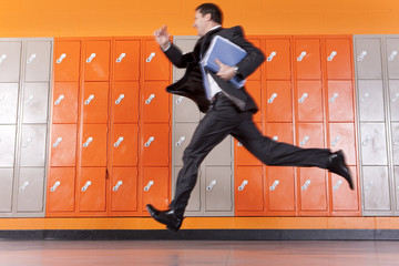 Serious teacher holding paperwork running past school lockers