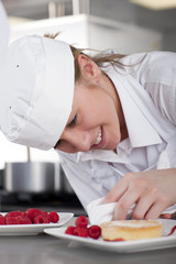Trainee chef wiping gourmet dessert in commercial kitchen