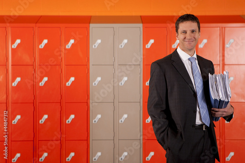 Smiling teacher holding paperwork near school lockers