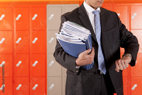 Teacher holding paperwork near school lockers and checking the time
