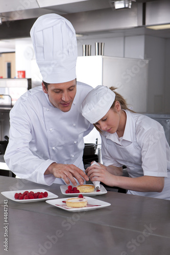 Chef teaching trainee how to garnish gourmet dessert in commercial kitchen