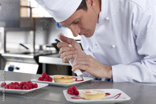 Chef decorating gourmet dessert in commercial kitchen