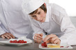 Teacher watching trainee garnishing dessert in commercial kitchen