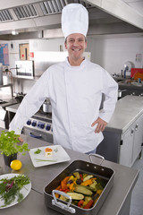 Smiling chef standing with vegetables in commercial kitchen