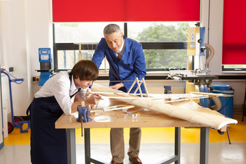 Teacher and student in woodworking class working on model airplane together