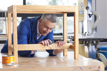 Carpenter in woodshop putting stain on wooden table