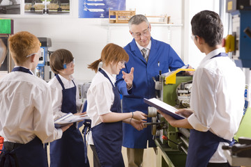 Teacher explaining to students how to use lathe in metalwork class
