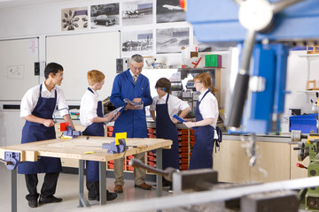 Teacher talking to students in vocational classroom