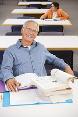 Portrait of smiling senior man studying in library