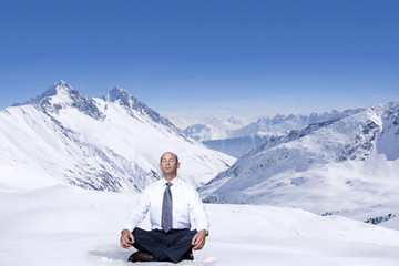 Businessman meditating in lotus position on snowy mountain top