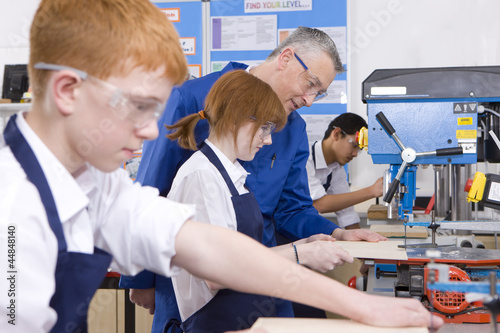 Teacher watching students use saw in woodworking class