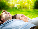 Fototapety Park. Young Couple Lying on Grass Outdoor