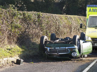 Wrecked car upside-down on roadside