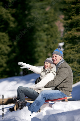 Smiling couple sitting on sled in snow