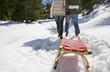 Couple pulling sled in snow covered wilderness