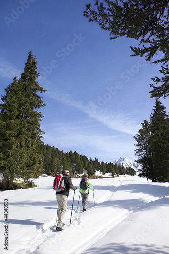 Couple hiking on trail in snow covered wilderness