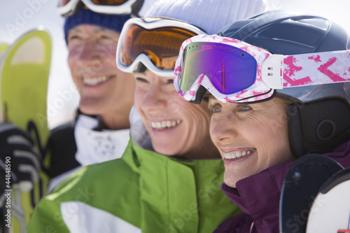 Smiling skiers standing in row