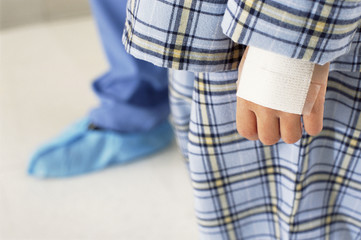 Close up of bandage on hand of boy in pajamas