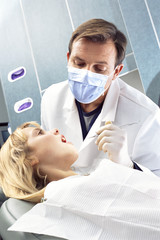 Dentist looking into girl's mouth