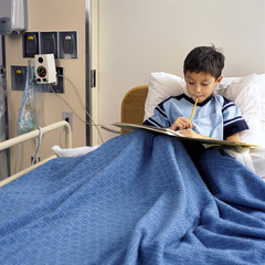 Boy in hospital bed reading medical chart