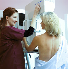 Nurse helping woman with mammogram in clinic