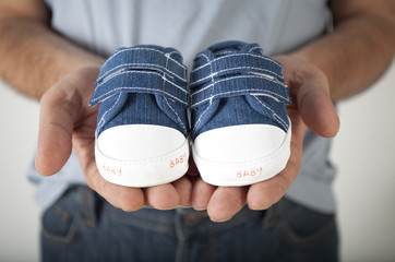 Man holding baby shoes