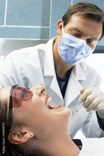 Close up of dentist looking into woman's mouth