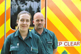 Portrait of smiling paramedics in front of ambulance