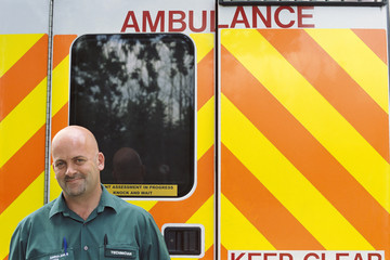 Portrait of smiling paramedic in front of ambulance
