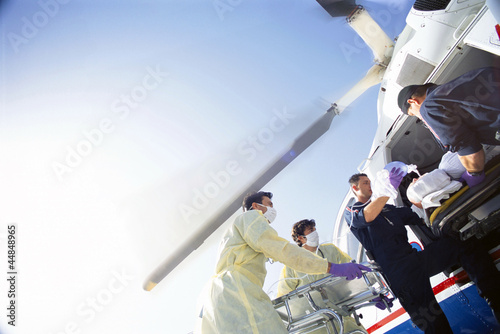 Doctors and paramedics transferring patient from emergency airlift helicopter