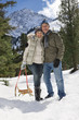 Portrait of happy senior couple with sled hugging in snowy woods