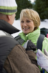 Close up of senior man helping woman with backpack in snowy woods