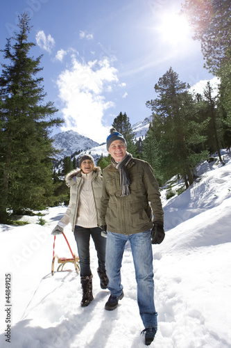 Portrait of happy senior couple with sled in snowy, sunny woods