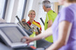 Personal trainer talking to senior man exercising on cross trainer in gym