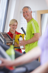 Portrait of confident senior man with water bottle on cross trainer in gym