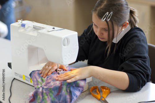 Girl using sewing machine in classroom